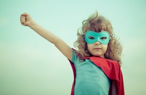 young girl dressed in superhero costume with arm outstretched