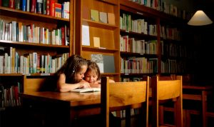 two girls sharing a book in a library