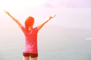 girl with arms outstretched looking across ocean