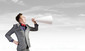 young man in business suit talking into a paper megaphone