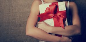 girl holding present with big red ribbon